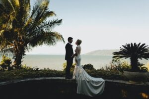 couple staring at each other at a garden in front of a beach signifies Villa Botanica's Romantic Beginning - Unique Wedding Venue Australia