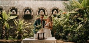 Villa Botanica garden queensland wedding venue with a cake in front of happy newly-wedded couple