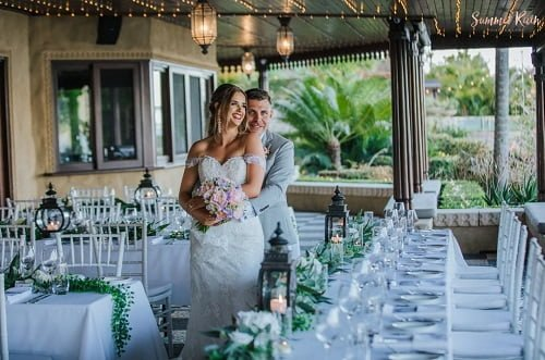 groom backhug bride in the middle of outdoor wedding venue with accents of overflowing greenery and glass candle to compliment Villa Botanica's backdrop