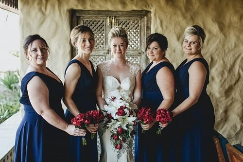 bride centered with bridesmaids wearing blue wedding dresses and holding bouquet of roses