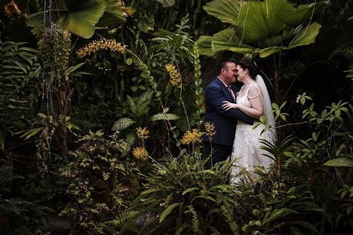 newlywed couple kissing with Villa Botanica's Garden Luxury Wedding