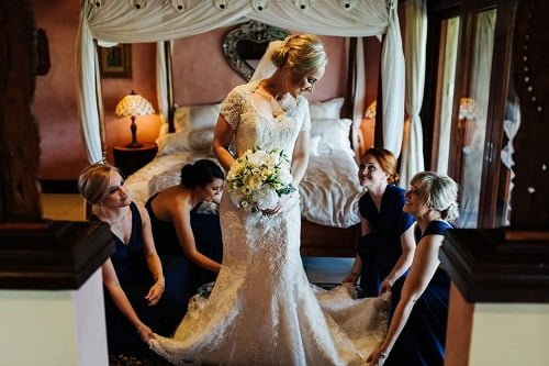 elegant bridesmaids helping a bride with her dress
