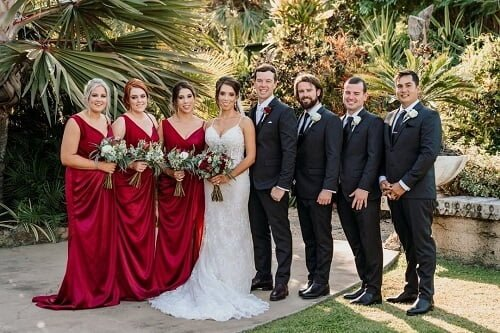 bride and groom having a luxury wedding with the bridesmaids wearing red and groomsman wearing black tuxedo