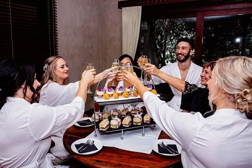 luxury wedding guests with the bride and groom doing cheers