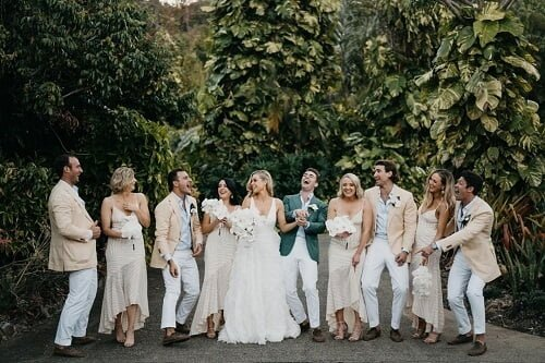 a group of laughing people composed of a bride and groom along with groomsmen and bridesmaids - Color Palette Trends 2021 Wedding Trends