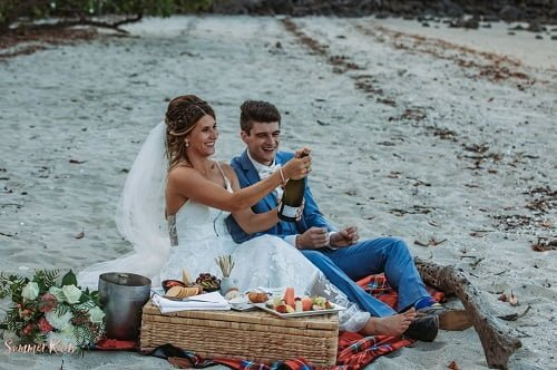 happy couple sitting on a beach sands with wedding catering foods provided at their whitsunday wedding venue