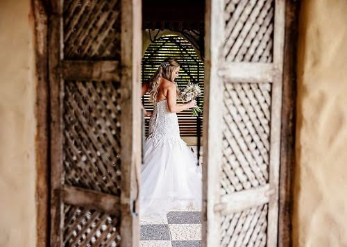 a bride wearing a white wedding gown dress behind an open wooden door